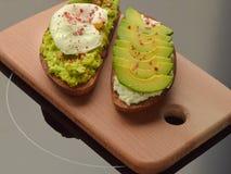 Brindes do abacate com ovo e queijo, suporte apenas em uma placa de desbastamento da faia fotos de stock