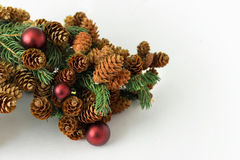 Brindille de pin avec des cônes avec les décorations rouges de Noël de boules Photos stock