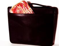 Bring home the bacon. Pound of bacon in a briefcase, conceptual idea for earning money royalty free stock images