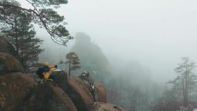 Bringen Sie Ansicht am Mann zur Sprache, der auf die Oberseite des Felsens in den Winterbergen sitzt, die mit Nebel bedeckt werde stock video