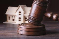 Bringen Sie Auktion, Auktionshammer, Symbol der Berechtigung und Miniaturhaus unter Gerichtssaalkonzept stockfoto