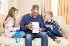 Bringen Sie das Öffnungsgeschenk hervor, das von den Kindern auf Sofa gegeben wird Stockfotografie