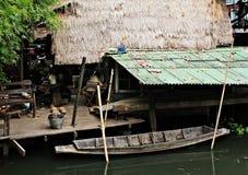 Bringen Sie das Dach unter, das vom Gras und vom alten Ruderboot hergestellt wird. Stockfotografie
