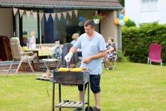 Bringen Sie das Grillen des Fleisches im Garten für das Mittagessen hervor stockfoto
