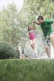 Bringen Sie das Halten der Tochterhand hervor, während sie durch die Berieselungsanlage im Garten springt Stockbilder