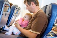 Bringen Sie das Halten seiner Babytochter während des Fluges auf dem Flugzeug hervor, das auf Ferien geht stockbilder
