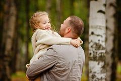 Bringen Sie das Halten seiner Tochter in einem reizend gelockte Beige gestrickten Schalter hervor lizenzfreies stockfoto