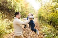 Bringen Sie das Halten seines kleinen Sohns hervor und ihn spinnen Lange Schatten und blauer Himmel Stockfotos