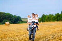 Bringen Sie das Halten von zwei Kindern auf Armen auf Weizenfeld im Sommer hervor stockfoto