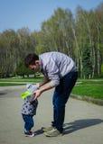Bringen Sie das Helfen seines Sohns für die ersten Schritte hervor lizenzfreie stockfotos
