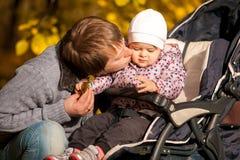 Bringen Sie das Küssen der Tochter hervor, die im Buggy am Park sitzt lizenzfreie stockfotografie