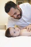 Bringen Sie das Küssen und das Spielen mit seinem netten Baby hervor Stockfotografie