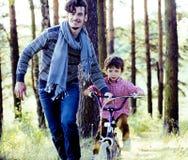 Bringen Sie das Lernen seines Sohns hervor, um auf Fahrrad draußen im grünen Park, Lebensstilleutekonzept zu fahren Lizenzfreie Stockfotografie