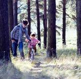 Bringen Sie das Lernen seines Sohns hervor, um auf Fahrrad draußen im grünen Park, wirkliche glückliche Familie, Lebensstilleutek Stockbild