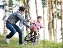 Bringen Sie das Lernen seines Sohns hervor, um auf Fahrrad draußen im grünen Park, wirkliche glückliche Familie, Lebensstilleutek Stockfoto