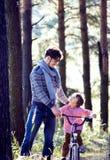 Bringen Sie das Lernen seines Sohns hervor, um auf Fahrrad draußen im Park zu fahren Lizenzfreie Stockbilder