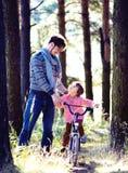 Bringen Sie das Lernen seines Sohns hervor, um auf Fahrrad draußen im Park zu fahren Stockbilder