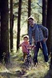 Bringen Sie das Lernen seines Sohns hervor, um auf Fahrrad draußen zu fahren Lizenzfreies Stockbild