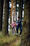 Bringen Sie das Lernen seines Sohns hervor, um auf Fahrrad draußen zu fahren Stockfoto