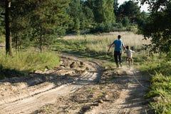 Bringen Sie das Lernen seines Sohns hervor, um auf Fahrrad draußen zu fahren Stockbilder