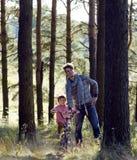 Bringen Sie das Lernen seines Sohns hervor, um auf Fahrrad draußen zu fahren Lizenzfreie Stockbilder