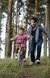 Bringen Sie das Lernen seines Sohns hervor, um auf Fahrrad draußen zu fahren Stockbild