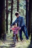 Bringen Sie das Lernen seines Sohns hervor, um auf Fahrrad draußen zu fahren Lizenzfreies Stockfoto
