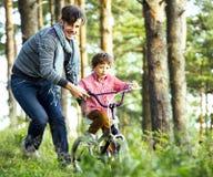 Bringen Sie das Lernen seines Sohns hervor, um auf Fahrrad draußen zu fahren, wirkliche glückliche Familie, Lebensstilleutekonzep Lizenzfreie Stockfotografie