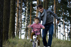 Bringen Sie das Lernen seines Sohns hervor, um auf Fahrrad draußen zu fahren, wirkliche glückliche Familie in Sommerwald-enjoing  Stockbilder