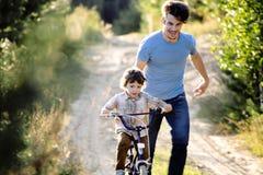 Bringen Sie das Lernen seines Sohns hervor, um auf Fahrrad draußen zu fahren, wirkliche glückliche Familie in Sommerwald-enjoing  Stockbild