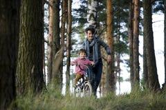 Bringen Sie das Lernen seines Sohns hervor, um auf Fahrrad draußen zu fahren, wirkliche glückliche Familie in Sommerwald-enjoing  Stockfotografie