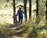 Bringen Sie das Lernen seines Sohns hervor, um auf Fahrrad draußen zu fahren, wirkliche glückliche Familie in Sommerwald-enjoing  Lizenzfreies Stockfoto