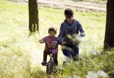 Bringen Sie das Lernen seines Sohns hervor, um auf Fahrrad draußen zu fahren, wirkliche glückliche Familie in Sommerwald-enjoing  Lizenzfreie Stockbilder