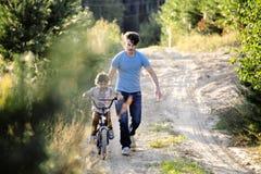 Bringen Sie das Lernen seines Sohns hervor, um auf Fahrrad draußen zu fahren, wirkliche glückliche Familie in Sommerwald-enjoing  Stockfoto