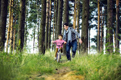 Bringen Sie das Lernen seines Sohns hervor, um auf Fahrrad draußen zu fahren, wirkliches glückliches f Stockfotos