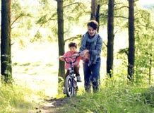 Bringen Sie das Lernen seines Sohns hervor, um auf Fahrrad draußen zu fahren, wirkliches glückliches f Stockbild