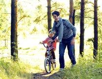 Bringen Sie das Lernen seines Sohns hervor, um auf Fahrrad draußen zu fahren, wirkliches glückliches f Lizenzfreies Stockfoto