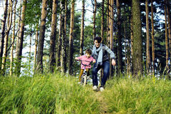 Bringen Sie das Lernen seines Sohns hervor, um auf Fahrrad draußen zu fahren, wirkliches glückliches f Lizenzfreie Stockfotos