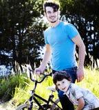 Bringen Sie das Lernen seines Sohns hervor, um auf Fahrrad draußen zu fahren, wirkliches glückliches f Stockfoto