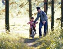 Bringen Sie das Lernen seines Sohns hervor, um auf Fahrrad draußen zu fahren, wirkliches glückliches f Stockfotografie