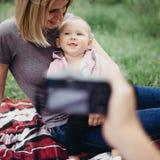 Bringen Sie das Machen von Fotos des kleinen Mädchens mit Mutter hervor Lizenzfreies Stockbild