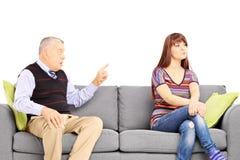 Bringen Sie das Reprimending seine uninteressierte Tochter hervor, die auf einem Sofa setzt Stockfotografie