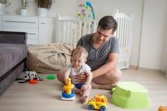 Bringen Sie das Sitzen auf Boden mit seinem Baby und das Spielen mit Spielwaren hervor Lizenzfreie Stockbilder
