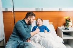 Bringen Sie das Spielen mit dem netten kleinen Sohn hervor, der im Krankenhausbett, -vati und -sohn im Krankenhaus liegt stockbild
