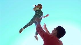 Bringen Sie das Spielen mit dem Tochtermädchen hervor, das in die Luft wirft clip Glückliches aktives Kinderkind Vater wirft sein Stockfoto