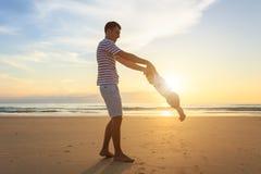 Bringen Sie das Spielen mit seinem Sohn auf dem Strand zur Sonnenuntergangzeit hervor aus stockbild