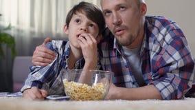Bringen Sie das Umarmen des kleinen Sohns während des aufpassenden Filmhauses mit dem Popcorn hervor, das auf Kind stolz ist stock video