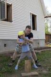 Bringen Sie das Unterrichten seines kleinen Sohns hervor, Brennholz zu hacken lizenzfreie stockfotografie