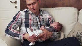 Bringen Sie das Vorlegen auf eine Socke seinem neugeborenen Baby hervor stock footage