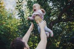 Bringen Sie das Werfen seiner kleinen Tochter in die Luft im Wald hervor lizenzfreie stockbilder